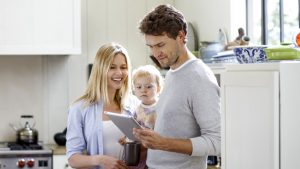 A family standing and looking at a tablet