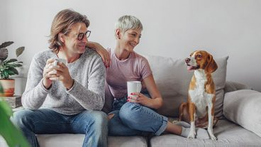 Man and woman sitting on a couch with a dog