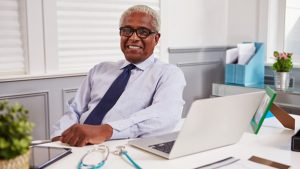 A man with an confident grin sitting at a laptop