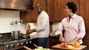 couple cooking in kitchen and smiling