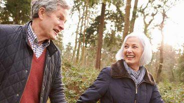 Older couple walk through the woods