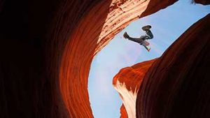Hiker jumping across a narrow canyon.