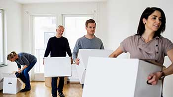 Adult children and parents carrying moving boxes