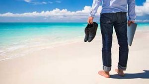 A man standing barefoot on a beach holds his shoes and a laptop.