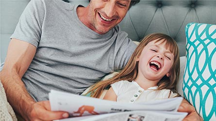 Man reads paper in bed with giggling daughter