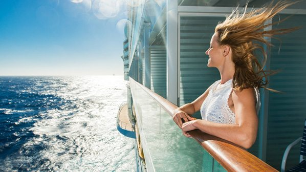 happy woman leaning on a cruise ship railing