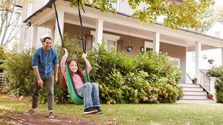 homeowner pushing daughter on swing
