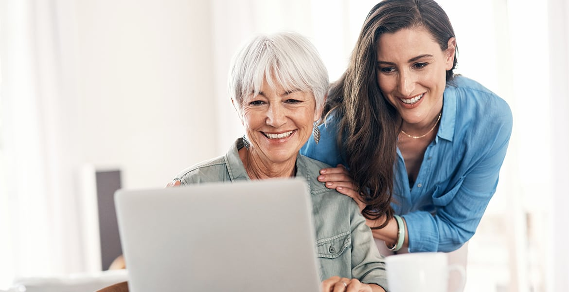 woman helping elder adult on computer