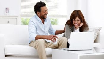 Happy couple looks at computer showing retirement options