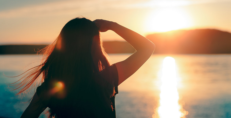 A woman peers at the sun near the horizon.