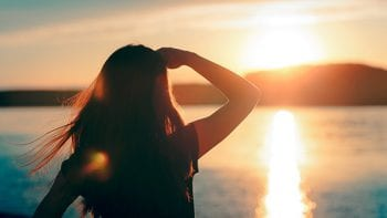A woman peers at the sun near the horizon.