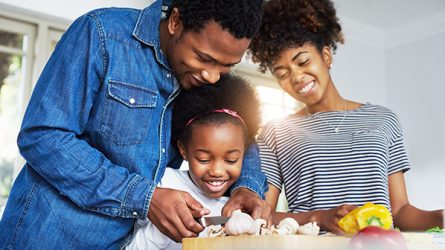 Financial savvy parents cook with young daughter at home.