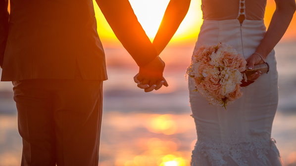 Newlywed man and woman holding hands in front of a sunset. Getting married is one reason to review beneficiary designations.