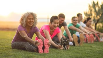 A group of people in fitness clothes do seated stretches outdoors. Healthy living can contribute to the need to plan for a longer, more expensive retirement.