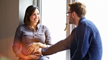 A man and a pregnant woman sit together in front of a window. Preparing for a baby should include financial plans.
