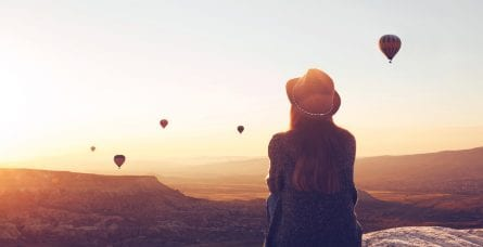 Woman seated on a hill watches hot-air balloons floating in the distance.