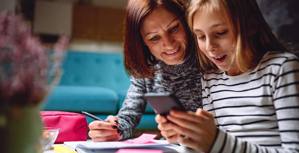 A woman and her daughter use a smartphone, a notebook, and sticky notes to discuss money and personal values.