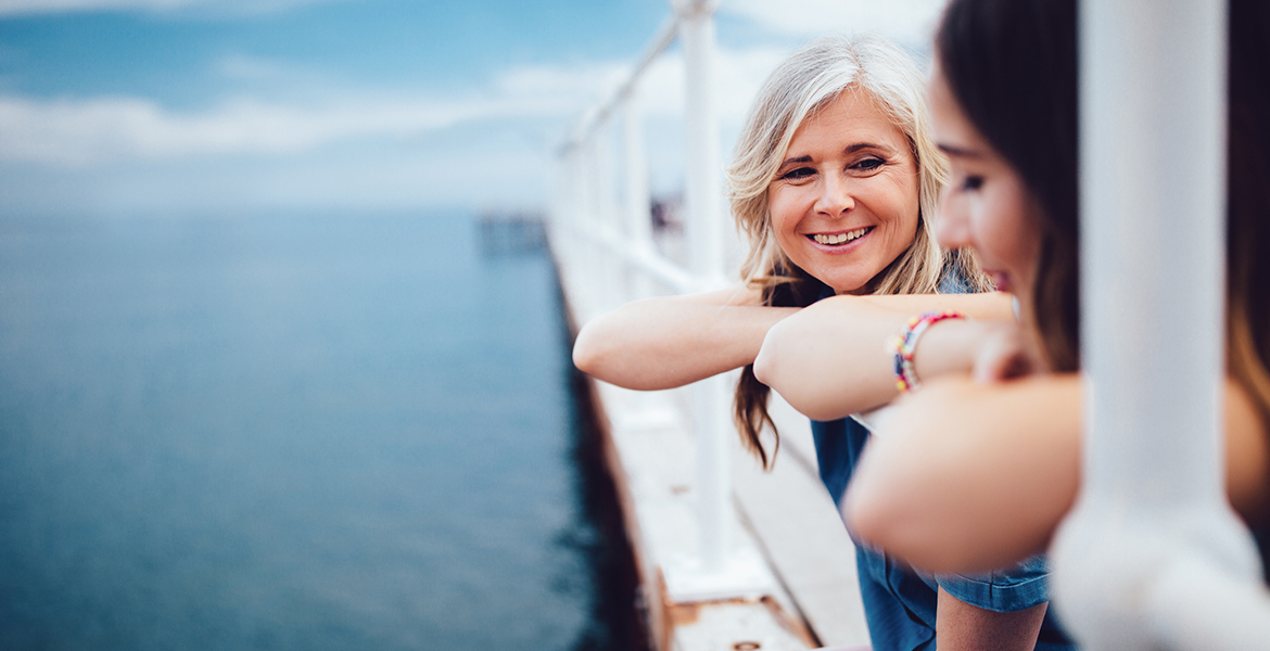 A woman and her daughter lean over a boat railing. Parents can help set the next generation on a path toward financial success.