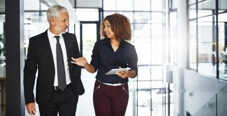 A male co-worker talks to a female co-worker holding paperwork.