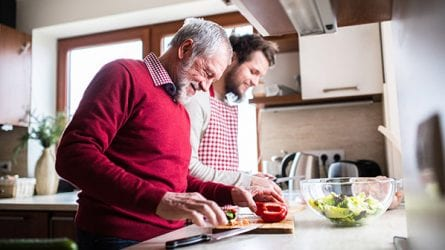 A man and his grown son make a salad together