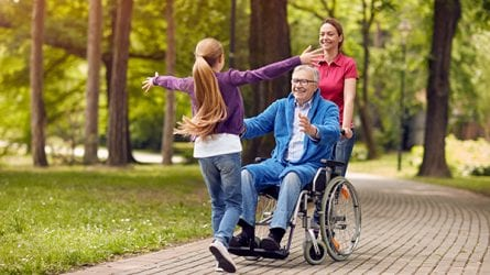 A girl rushes to hug her grandfather seated in a wheelchair while her mother watches.