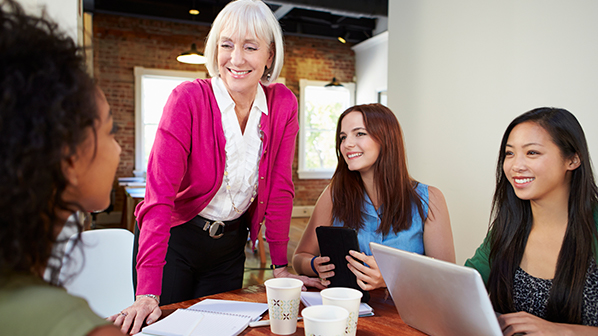 A senior female employee reviews a plan with her coworkers.