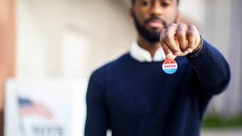 "A man holds a sticker that says, ""I voted today."""