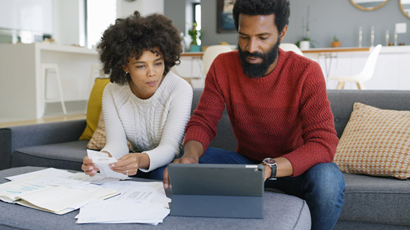 A man and woman sitting on a couch review paperwork together.