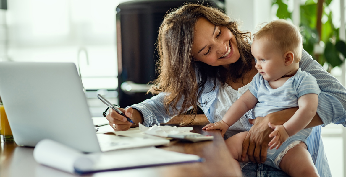 A mother holds her baby while seated at a table near a laptop and paperwork.