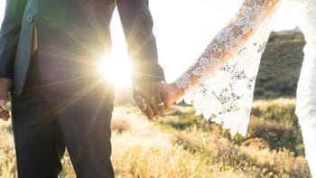 A man and a woman just married hold hands outdoors.