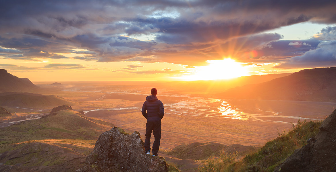 A man standing on a mountain peak looks at the sun peeking through the clouds.