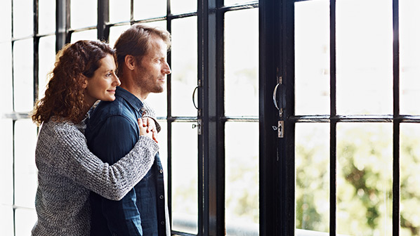 A woman and a man look out a window.