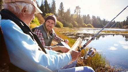 Two men are fishing at a pond.