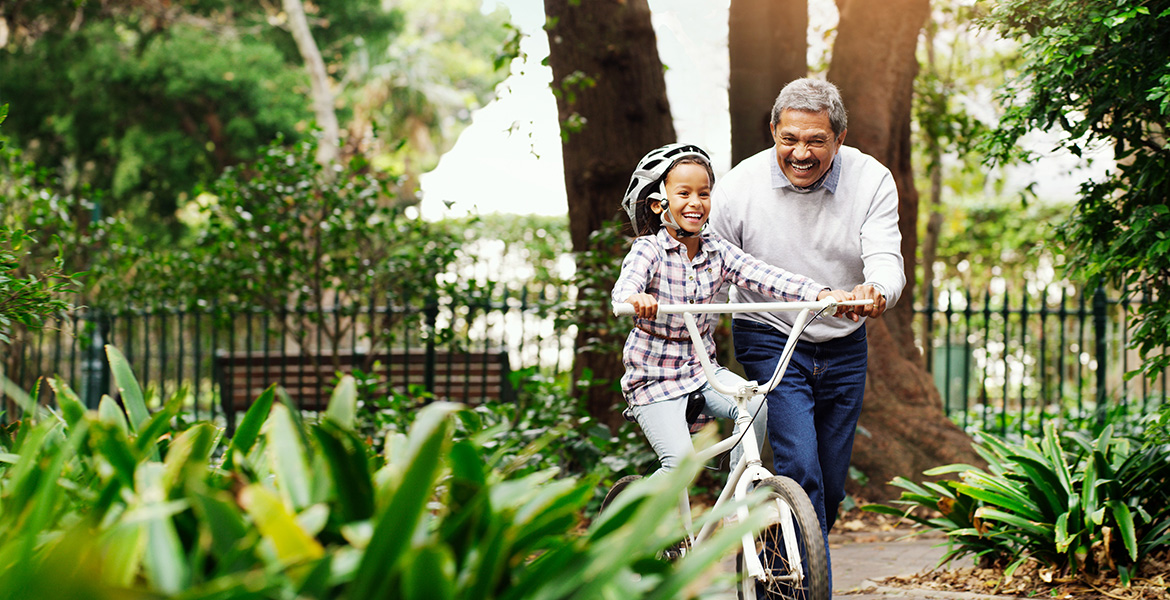 A man helps his grandchild ride a bicycle.