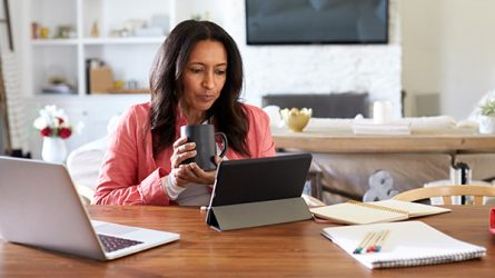 A woman holding a cup looks at her tablet.