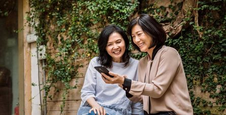 Two women look at a smartphone.