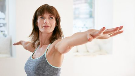 A woman performs the yoga warrior pose