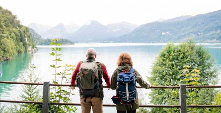 A man and woman look out over a lake during a hike.