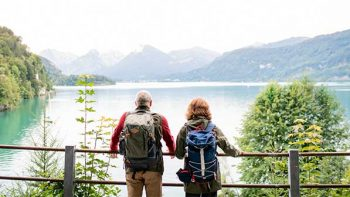 A man and woman stare at a lake during a hike.
