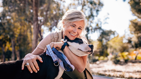 A woman holds her dog.