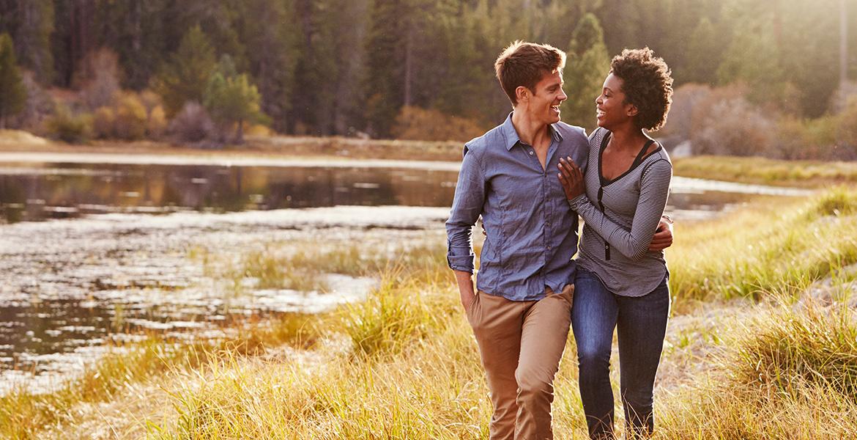 A couple takes a walk by a lake.